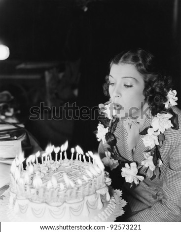 Profile of a young woman blowing off candles on a birthday cake - stock photo