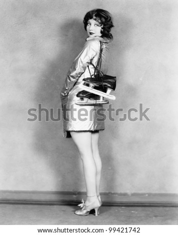 Profile of a young woman carrying ice-skates on her shoulders - stock photo