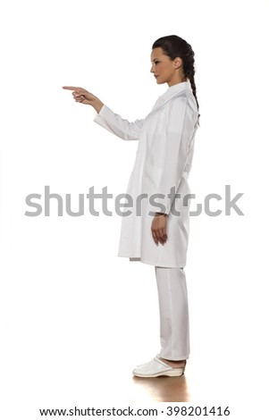profile of a young woman doctor in uniform pointing on empty