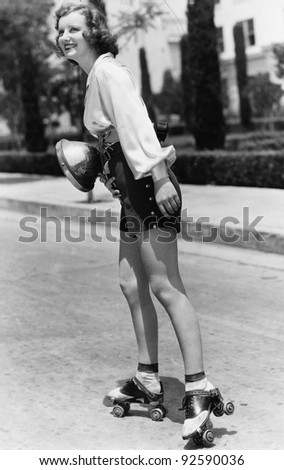Profile of a young woman roller skating on the road - stock photo