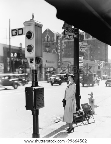 Profile of a young woman standing near a stop light - stock photo