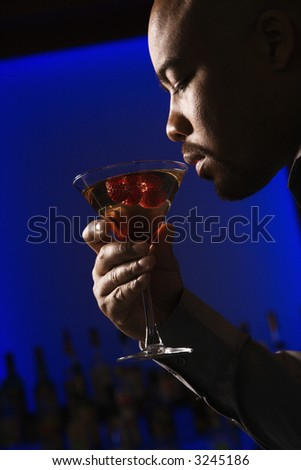 Profile of African American man drinking martini in bar against glowing blue background.
