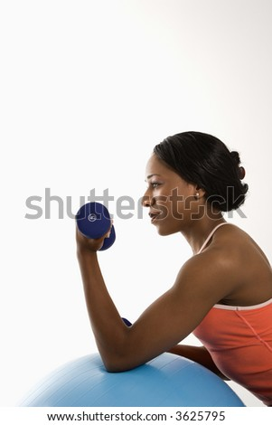 Profile of African American young adult woman leaning on exercise ball holding dumbbell. - stock photo