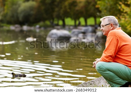 Profile of aged man in glasses sitting near pond in park watching ducks - stock photo
