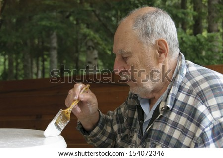 profile of aged senior man with expressive face painting carefully  a garden  table - stock photo