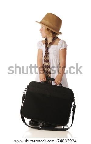 Profile of an adorable preschooler  holding a computer while wearing a sundress and an old-style felt hat, wide tie and men's shoes.  Isolated on white. - stock photo