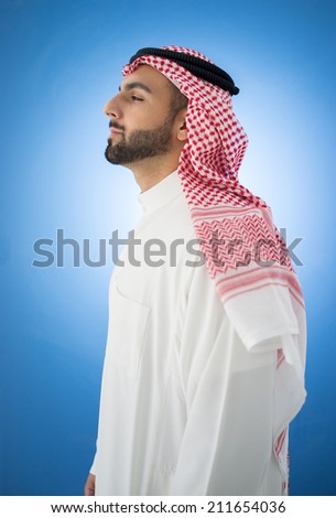 Profile of Arabic businessman on blue wall - stock photo