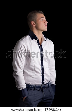 Profile of attractive young man with white shirt, hands in pockets, looking to a side - stock photo