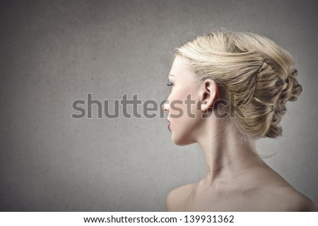 profile of beautiful blonde woman on gray background - stock photo