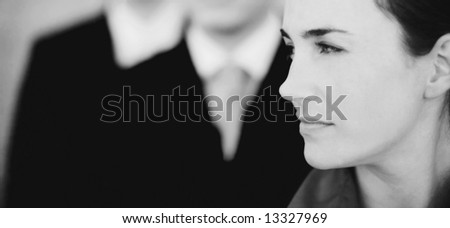 profile of beautiful businesswoman with two businessmen in the background - stock photo