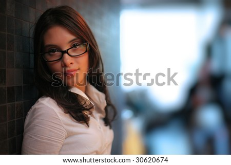 Profile of beautiful young brunette woman indoors. Shallow DOF. - stock photo