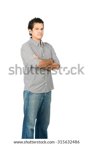 Profile of critical, judgmental hispanic man in casual clothes with arms crossed looking at camera expressing stoic, harsh, unhappy, disappointed attitude. Vertical - stock photo
