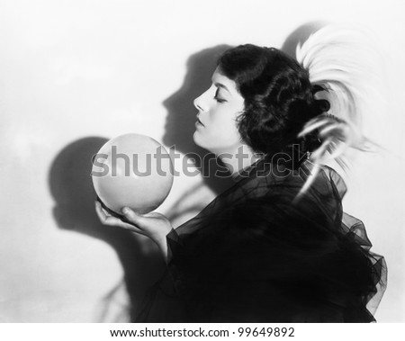 Profile of dramatic woman holding sphere - stock photo