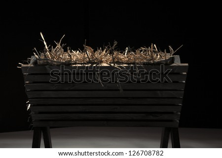 Profile of empty wooden manger filled with hay. - stock photo