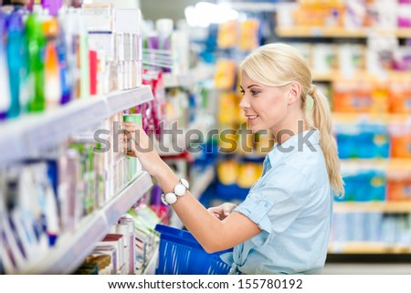 Profile of girl at the shop choosing cosmetics among the great variety of products. Concept of consumerism, retail and purchase - stock photo