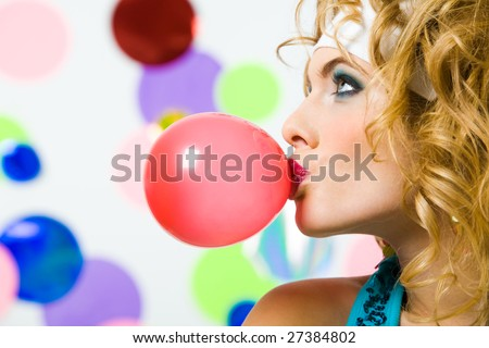 Profile of gorgeous female blowing chewing gum on colorful background
