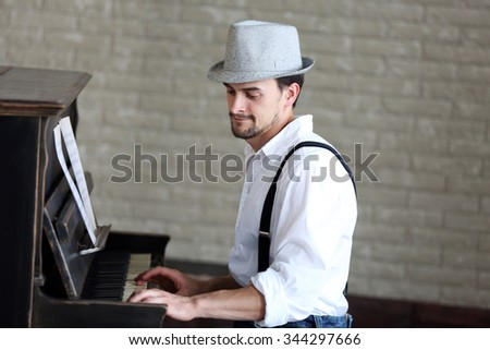 Profile of handsome young man in hat making piano music - stock photo