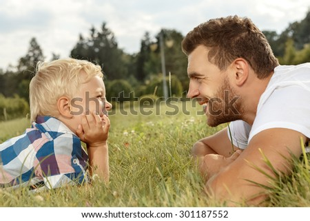 Profile of happy young father and son in the park - stock photo