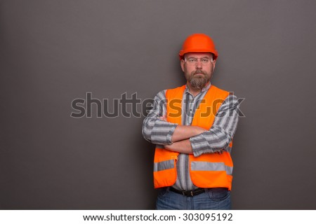 Profile of hipster bearded builder with his arms crossed. Man in orange helmet and protective jacket posing seriously on dark grey. - stock photo