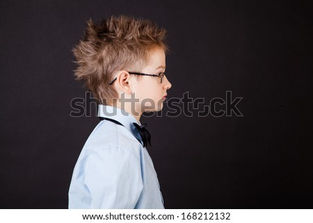 Profile of little boy over the black background