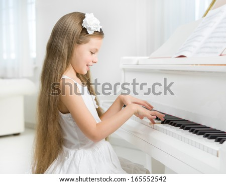 Profile of little girl in white dress playing piano. Concept of music study and art - stock photo
