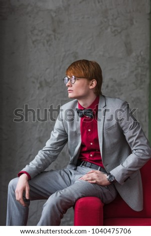 Profile of male model in eyeglasses dressed in suit sitting on edge of couch