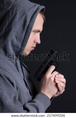 profile of man criminal with gun over grey background - stock photo