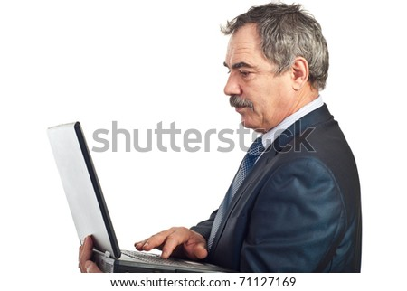 Profile of mature serious business man typing on laptop isolated on white background - stock photo
