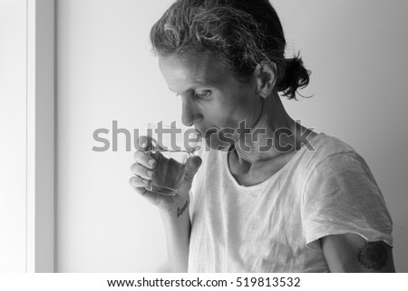Profile of middle aged woman holding glass and looking pensive - addition concept (black and white)