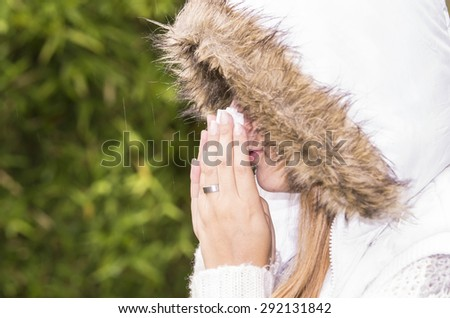 Profile of model in outdoors environment wearing hoodie and blowing her nose