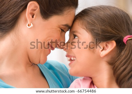Profile of mother and daughter touching noses