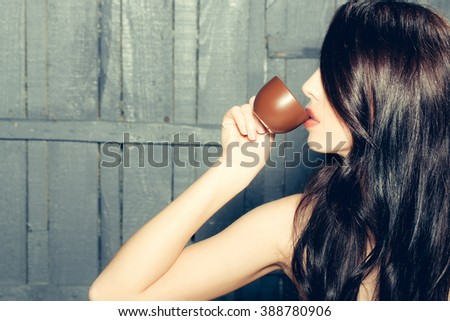 Profile of sensual attractive young woman with long brunette lush hair and bright lips drinking coffee from cup on wooden background, horizontal picture - stock photo