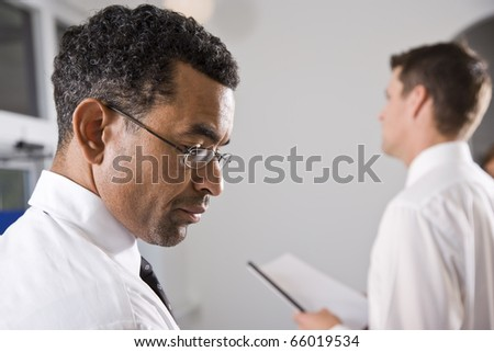 Profile of serious African American businessman, 40, looking down, colleague in background - stock photo