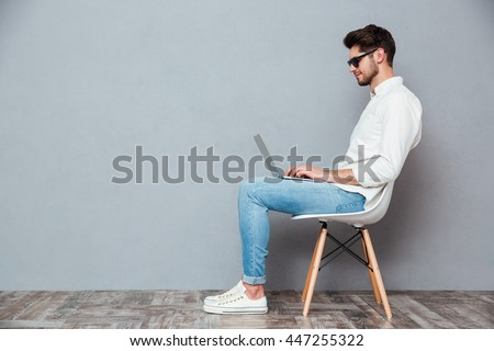 Profile of serious young man in sunglasses sitting on chair and using laptop over grey background