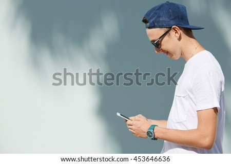 Profile of smiling high school student boy wearing shades and snapback holding mobile phone, messaging via social networks, posing against white copy space wall for your text or advertising content - stock photo