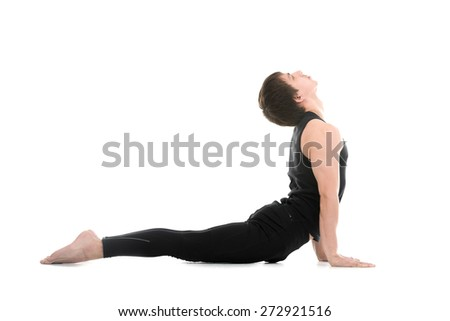 Profile of sporty young man working out, doing exercises for flexible spine, yoga asana from Surya Namaskar, Sun Salutation complex on white background - stock photo