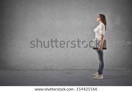 profile of student with laptop on a gray background - stock photo
