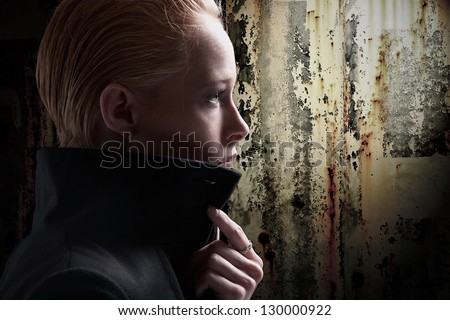 Profile of stylish young woman with dark grunge background