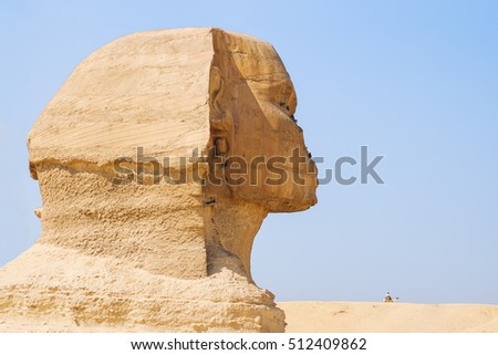 Profile of the great Sphinx. Landscape with ruined statue and a bedouin on a camel. Giza, Egypt.