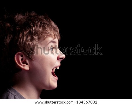 Profile of the shouting boy on a black background - stock photo
