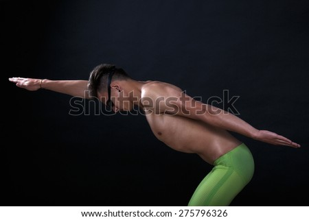 Profile of young , caucasian athlete swimmer with goggles in start position - stock photo