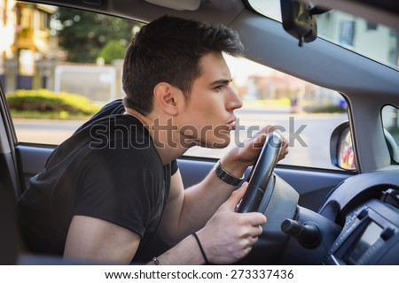 Profile of Young Man Driving Car and Leaning Forward and Peering Through Car Windshield - stock photo