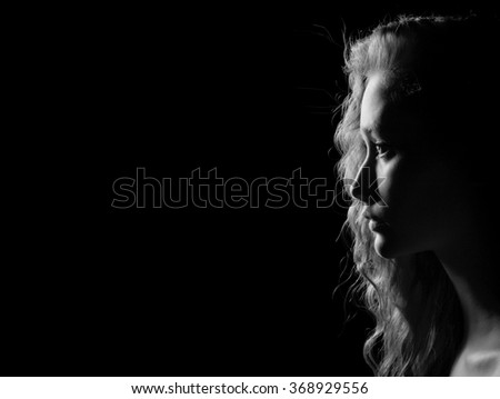 profile of young pensive woman on black background with copyspace, monochrome - stock photo