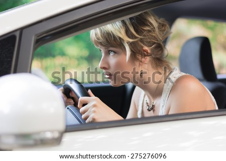 Profile of Young Woman Learning to Drive a Car, Leaning Forward and Peering Through Car Windshield - stock photo