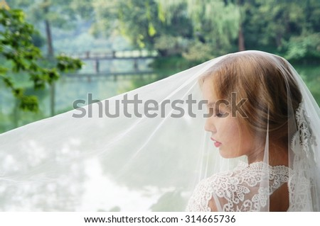 Profile picture of women wearing a wedding veil - stock photo