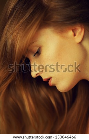 Profile portrait of a beautiful red-haired (ginger) girl with freckles on her face. Healthy long and wavy hair. Daylight. Close up. Studio shot