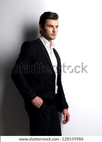 Profile portrait of a Fashion young man in black suit posing at  studio - stock photo