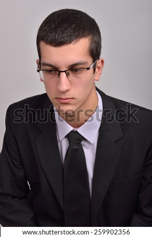 Profile portrait of a fashion young man with glasses in black suit posing in studio - stock photo