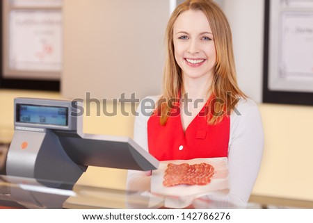 Profile portrait of a female worker, welcoming with a beautiful smile at the cash counter in a supermarket. - stock photo