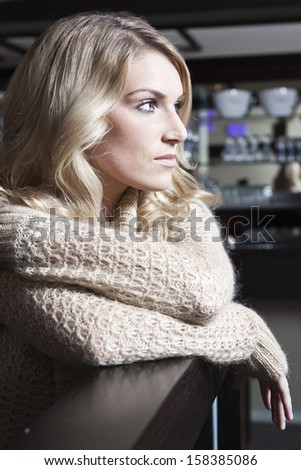 Profile portrait of a sad young blond woman wearing a cardigan pullover leaning over a table - stock photo
